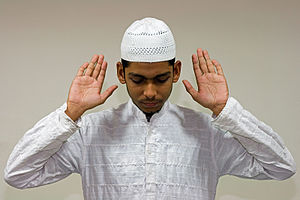 A Muslim raises his hands in Takbir, marking t...