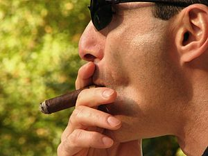 English: Man smoking a cigar.