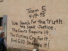 """A woman, at the left of the image, is reading a black spray paint message written on a brick wall. The message reads """"Team 5 4-19-95 We Search For the truth We Seek Justice. The Courts Require it. The Victims Cry for it. And God Demands it!"""""""