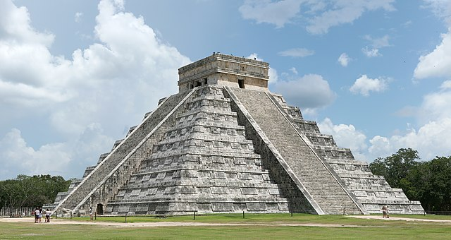 A huge stepped pyramid carved from grey stone, with a flat rectangular platform at the top.