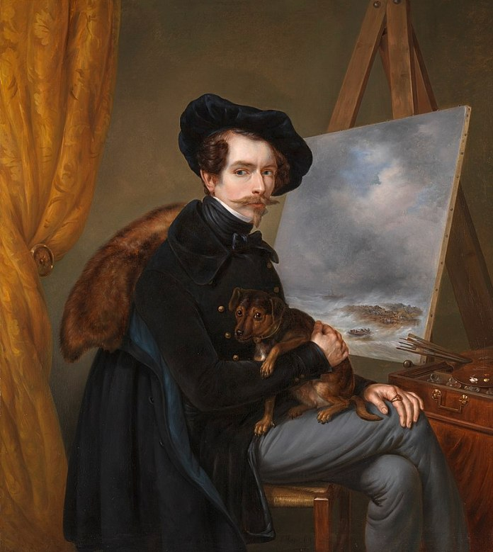 Louis Meijer seated with legs crossed while holding a dog in front of a painted canvas.