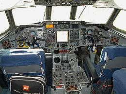The flight deck of a jet airliner with many instruments and controls. Two pilots' seats have small bags hanging on them, one has the words 'British European Airways'.