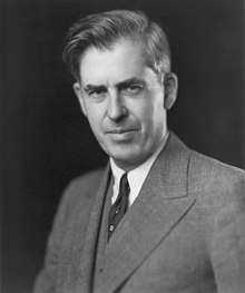 Head and shoulders of man about fifty with upswept hair, wearing a gray suit and dark tie
