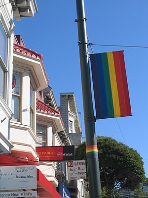 English: A rainbow flag affixed to a lightpole...