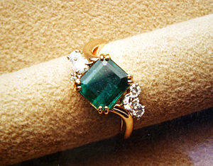 A faceted emerald cut emerald mounted in a com...