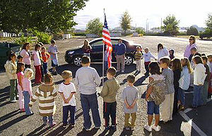 Elementary kids gather around the American fla...