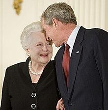 Con una sonrisa resplandeciente mirando al presidente.