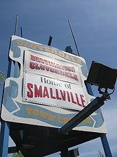 """Een wit bord met Een blauw lint rond de Randen.  Op het lint, """"Cloverdale Town Centre"""" verschijnen in Het geel rond Twee banners.  De top banner Leest, """"Destination Cloverdale"""" en de bodem leest, """"Huis van Smallville""""."""