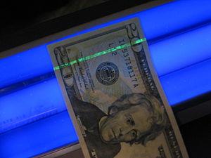 A U.S. $20 bill under a blacklight, showing th...