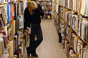 Woman browse books on an unknown library.