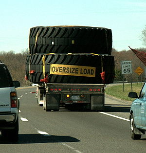 English: Three huge tires on a flatbed truck -...