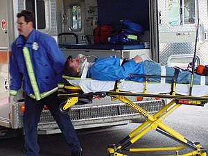 Medical personnel using a stretcher-type gurney.