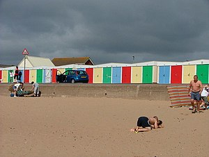 English: Colourful beach huts against a black sky
