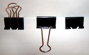 Three binder clips, one with the arms up, one ...