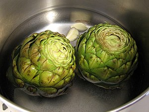 Globe artichokes being cooked with whole garli...