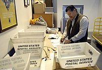 Enrique Garza sorts through incoming mail paym...