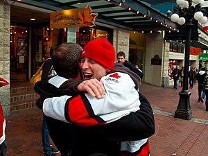 An emotional man grabs his friend in a burst o...