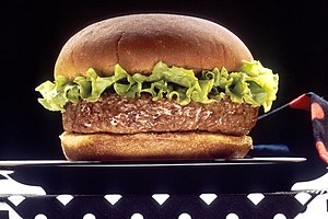 A hamburger with a rim of lettuce sitting on a...