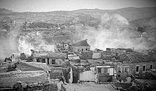 Des habitations en ruine, avec la fumée qui en sort.