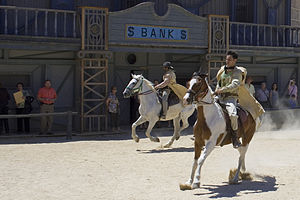 English: Cowboy actors ride off on their horse...