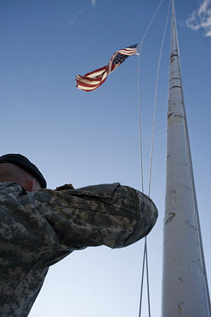 A Soldier renders honors to the American flag ...