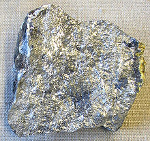An irregular piece of silvery stone with spots of variation in lustre and shade.