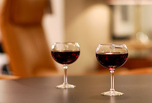 A pair of wine glasses with unidentified red w...