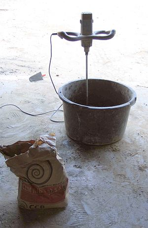 English: A bag of Portland cement being mixed ...