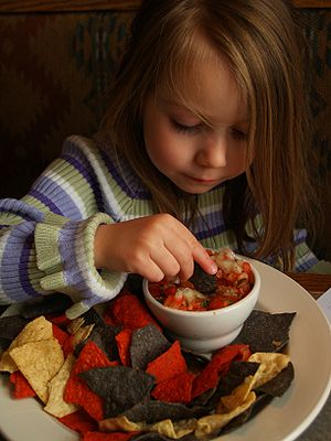 English: A young girl enjoys pico de gallo and...