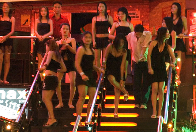 Prostitutes outside gogo bar in Thailand, Author Kay Chernosh for the US State Dept., Source Images of Human Trafficking https://gtipphotos.state.gov/photos.htm (PD)