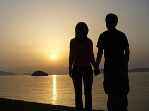 A Japanese couple holding hands on the beach