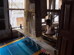 English: Weaver in a silk weaving workshop; Va...