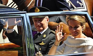 King Philippe and Queen Mathilde wave to the crowds in Brussels after Philippe's swearing in as new Belgian monarch.