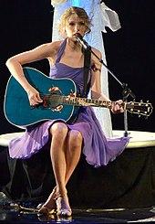 Taylor Swift, Gekleed in Een paarse jurk, Speelt Een blauwe Akoestische gitaar zittend op Een kruk