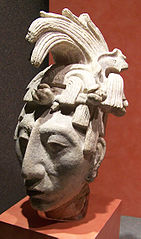 A carving of a man's head with an elaborate headdress.