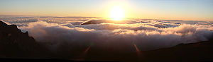 The sun rises from the clouds over Maui, taken...
