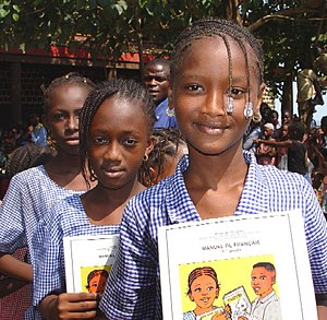 Schoolgirls with books donated by USAID in Con...