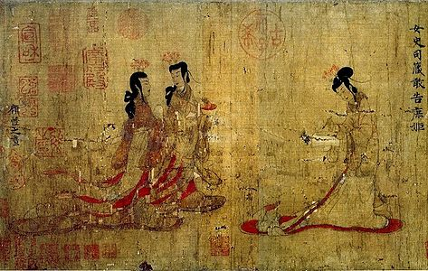 Two ladies walking towards another lady standing at a writing table with a writing brush in her hand