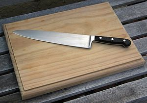 A wooden chopping board with a chef's knife.
