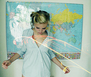 Young woman with map and light effects.