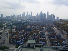 The port of Singapore with a large number of shipping containers with the skyline of the city visible in the background