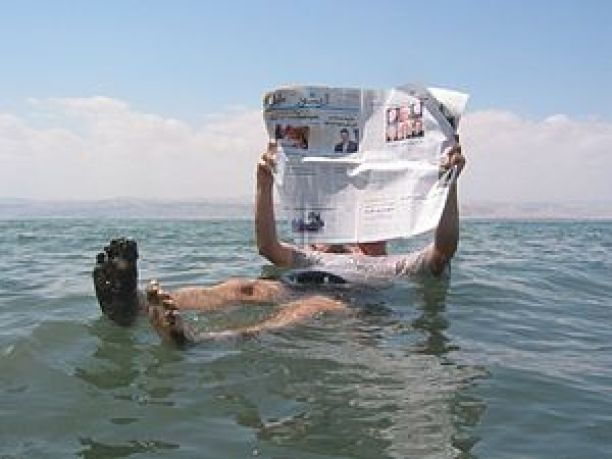 Man reading a newspaper in the Dead Sea.