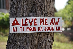 English: Sign in Guadeloupe creole on tree in ...
