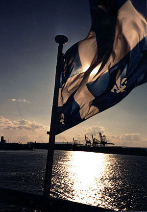 Quebec flag leads a ship to harbour near Quebe...