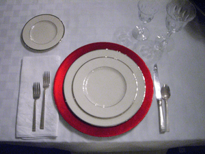 English: Place setting with red charger.
