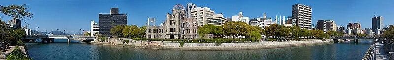 Vista de 180° del Parque Memorial de la Paz de Hiroshima. La Cúpula Genbaku, la cual permaneció en pie después del bombardeo, se ve claramente al centro de la imagen. El blanco original era el puente Aioi, a la izquierda en la vista panorámica.