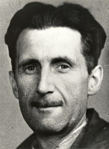 A photo showing the head and shoulders of a middle-aged man with black hair and a slim moustache.