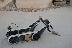An iRobot PackBot picks up a demonstration obj...