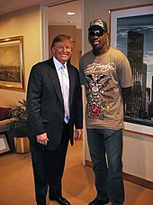 Donald Trump posing with basketball personality Dennis Rodman in a room with paintings adorning the walls. Trump is wearing a suit with a light-colored tie and dress shirt, while Rodman is wearing a brown t-shirt with a design on it, blue jeans, and a baseball cap that also has a design on it.