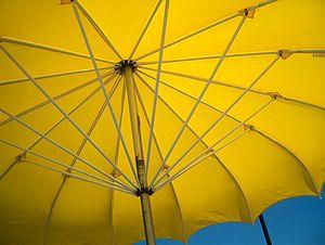 Yellow beach umbrella in the summer sun.